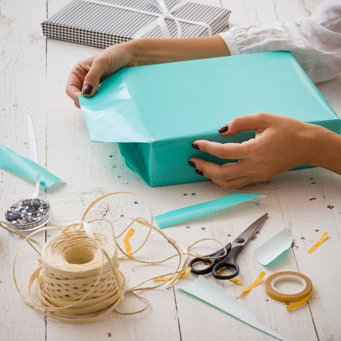 Closeup Of A Young Woman's Hands Wrapping A Festive Gift In A Turquoise Paper For A Birthday Or Any Other Event. Ribbons, Stars, Paper, Scissors And A Gift Lie On A White Wooden Table. Festive Concept